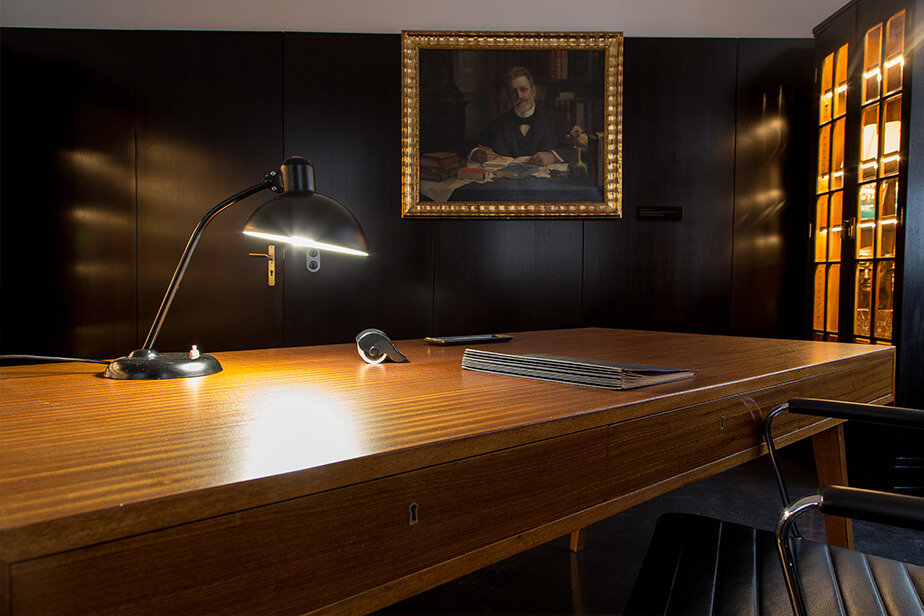 The photo shows the historical Rector's Room at Universität Hamburg, replete with a fine wood desk, antique desk lamp, and a painting in the background.