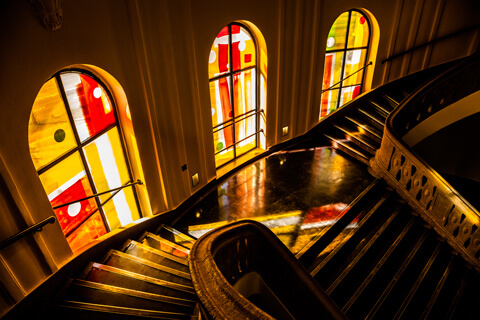 The photo shows the colored windows bathing the Main Building's stairwells in yellow and orange light.